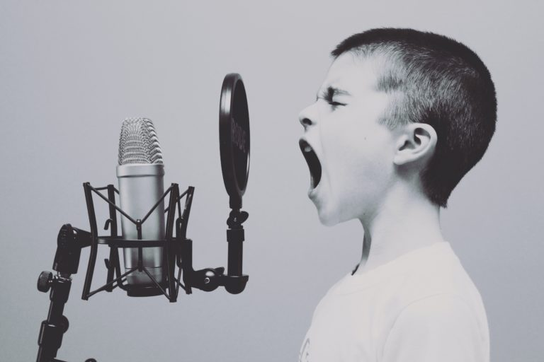 boy telling into microphone