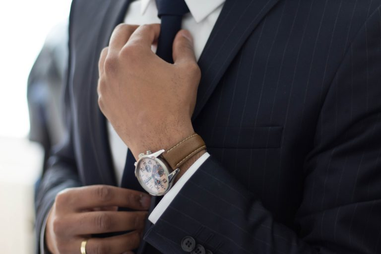 Man wearing a blue business suit considers the habits of self-aware business leaders