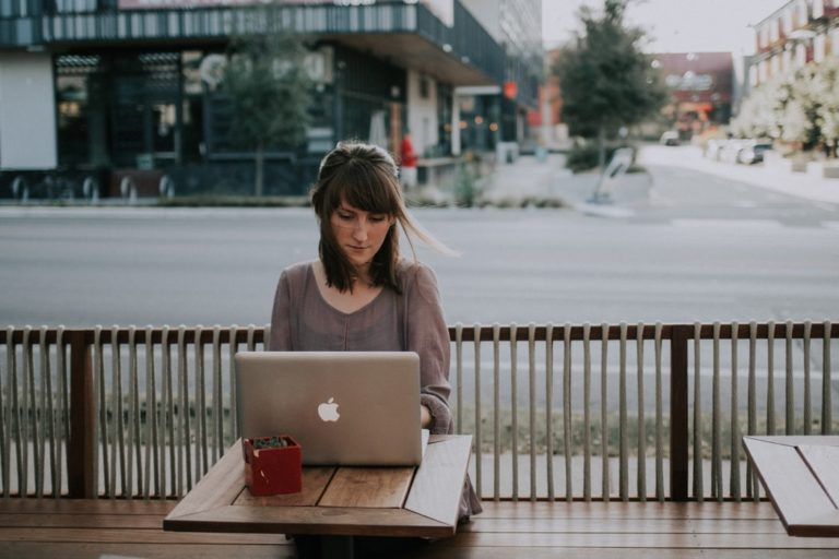 Distracted woman answers email on vacation and struggles with the value of paid time off