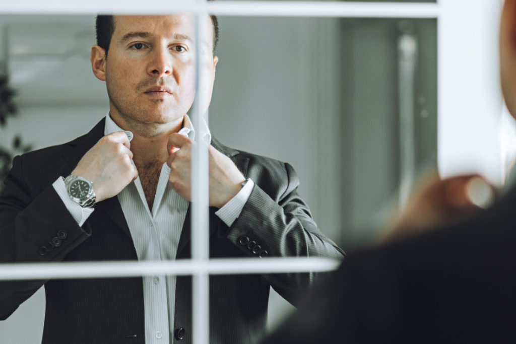 stoic man adjusting his shirt in a mirror reflects the stereotype of how emotionless leadership hinders effectiveness