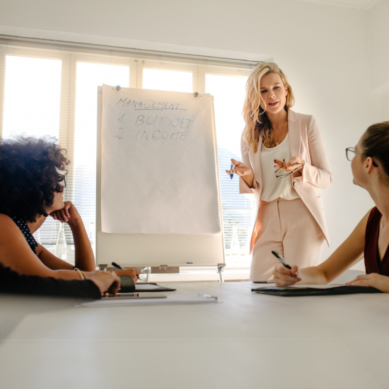 Tension fills the room while a female boss presents at a meeting